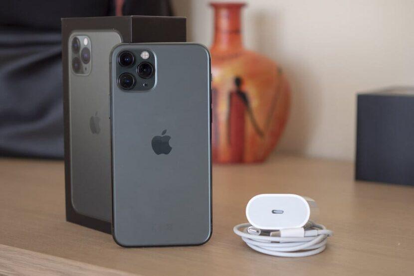 на столе серый айфон с коробкой и наушники