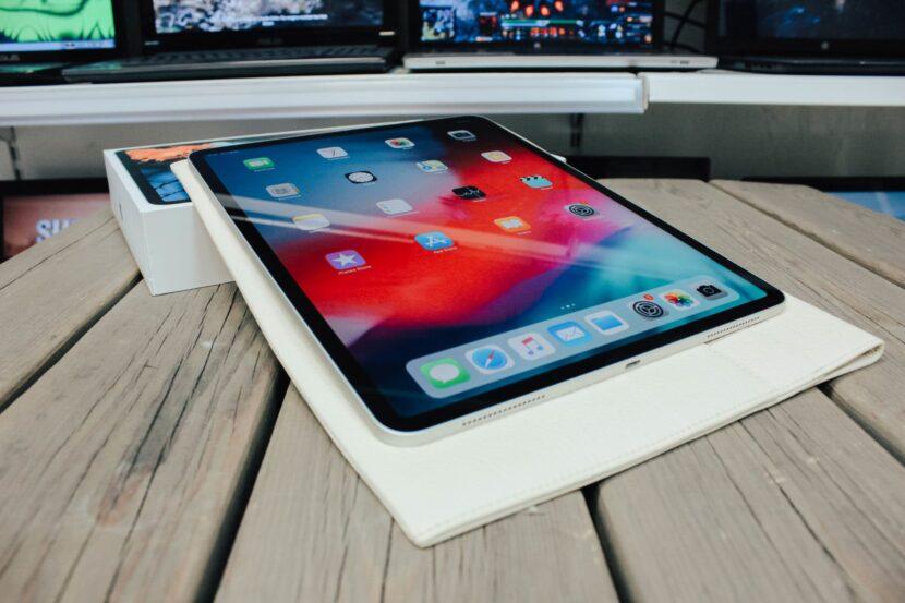 беленький iPad Pro в чехле на столе с коробкой