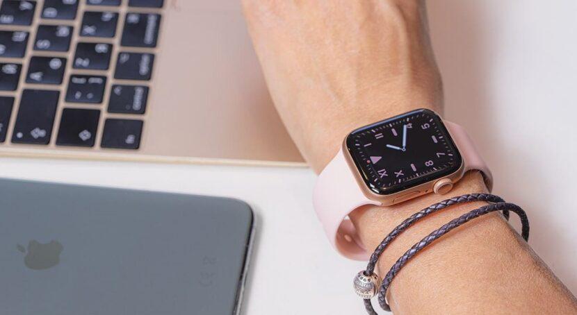 телефон и светло-розовые часы на руке