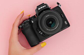 фотоаппарат у девушки в руке на розовом фоне